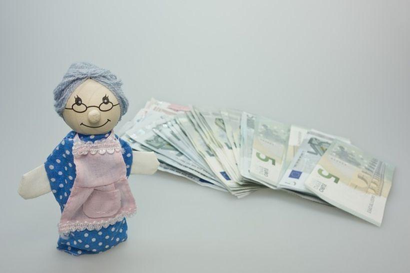 plišana igračka bake pored snopa novčanica