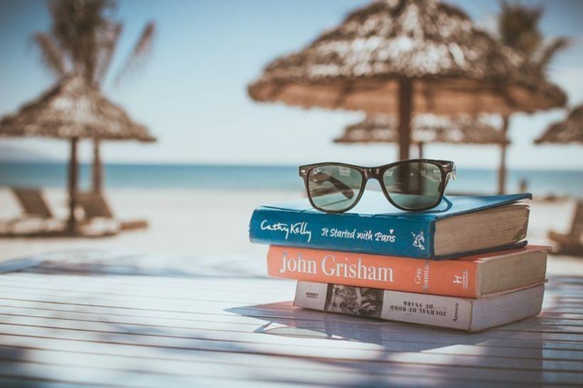 tri knjige, s naočalama na vrhu, na plaži