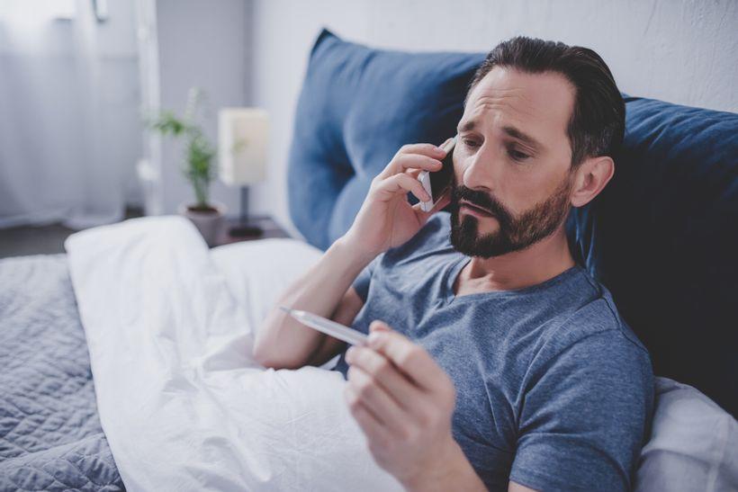 čovjek, omotan u deku, sjedi na kauču i priča na mobitel