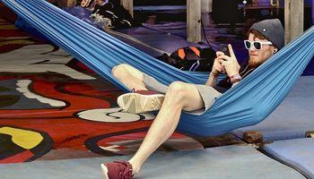 muškarac s naočalama  sjedni na visećoj mreži za spavanje