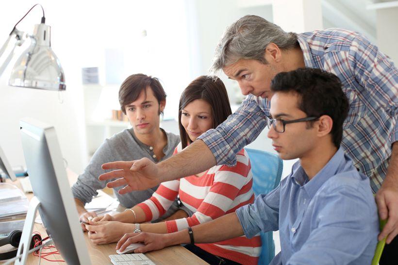 troje mladih ljudi zajedno s mentorom gledaju u računalo