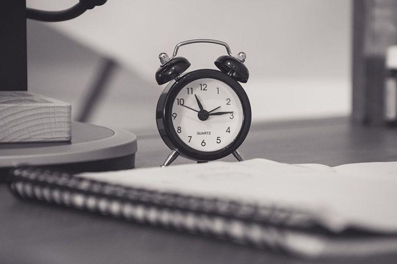 sat i bilježnica na radnom stolu