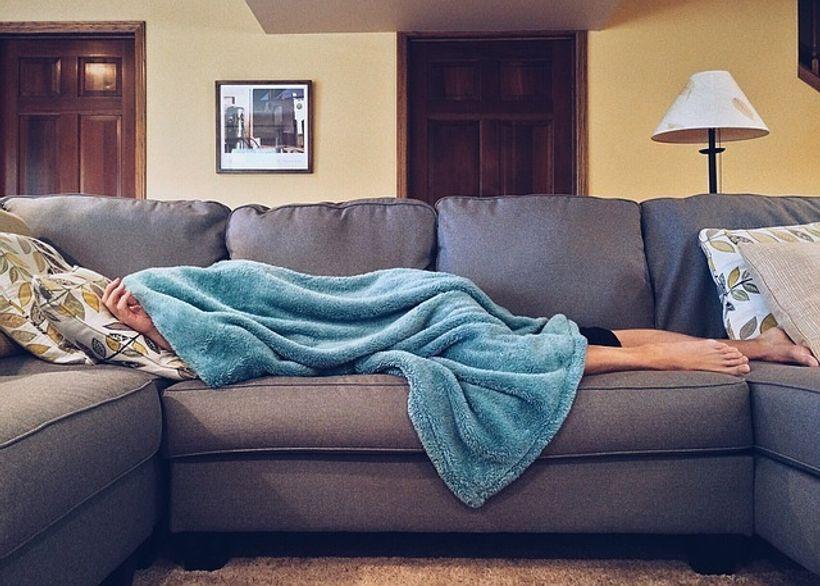 osoba, pokrivena plavim pokrivačem, leži na kauču