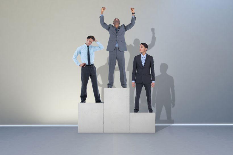 Tri čovjeka u odijelima stoje na podiju