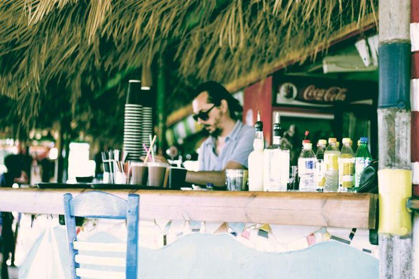otvoreni šank s pićem i konobar u pozadini