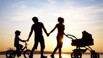 siluete muškarca, žene, djeteta na bicikli i kolica za bebu