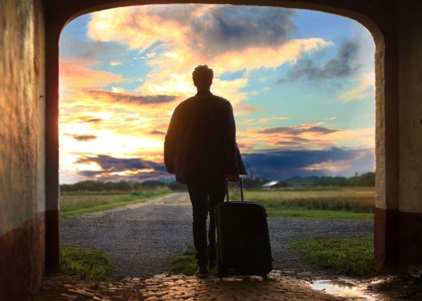 Muškarac s koferom izlazi iz tunela i odlazi u prirodu