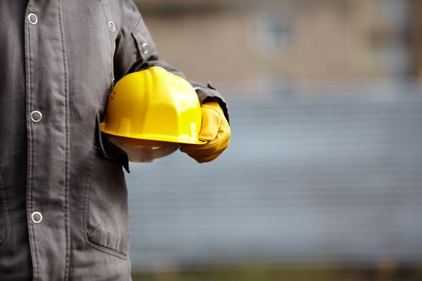 osoba u sivom radnom kombinezonu u ruci drži žutu kacigu