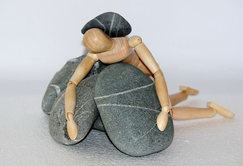 drveni čovjek zatrpan kamenjem