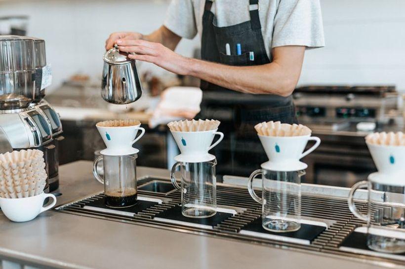 konobar toči kavu u više spremnika