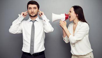 Žena s megafonom se dere na muškarca s prstima u ušima