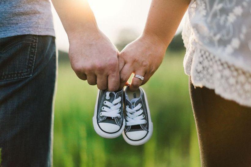 muška i ženska ruka sa dječjim tenisicama