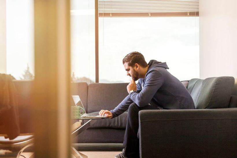 čovjek, zavaljen na kauču, radi na laptopu