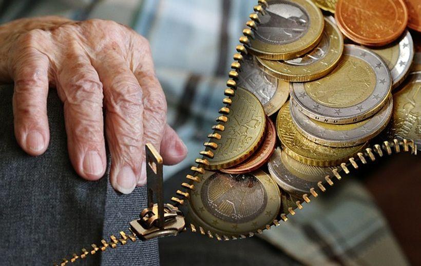 ruke starije osobe i kovanice eura