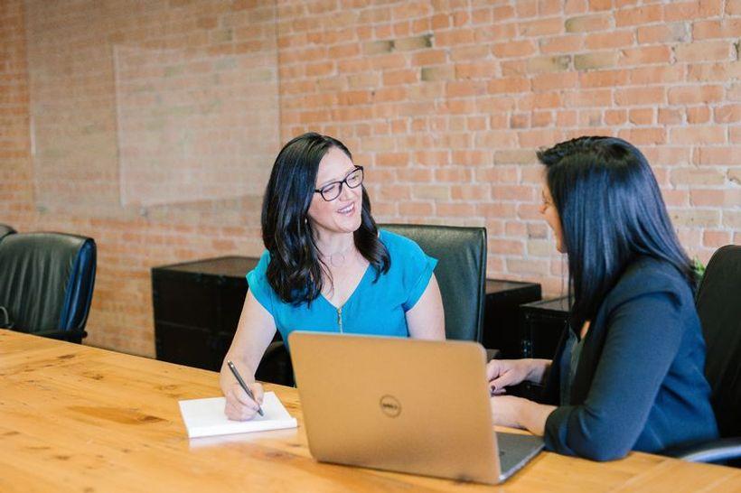 dvije žene sjede za stolom i razgovaraju
