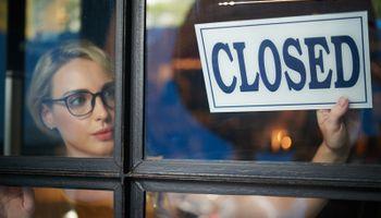 djevojka na staklena vrata postavlja znak 'closed'