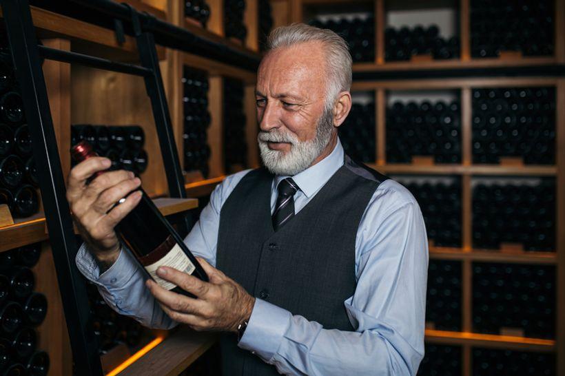 Stariji gospodin u rukama drži butelju vina