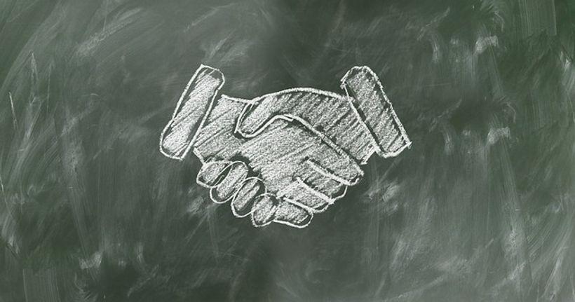 školska ploča na kojoj se dvije, kredom nacrtane, ruke rukuju