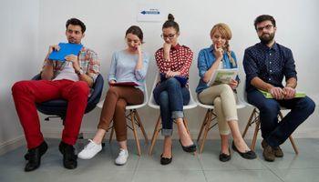 petero ljudi u čekaonici sjede na stolcima