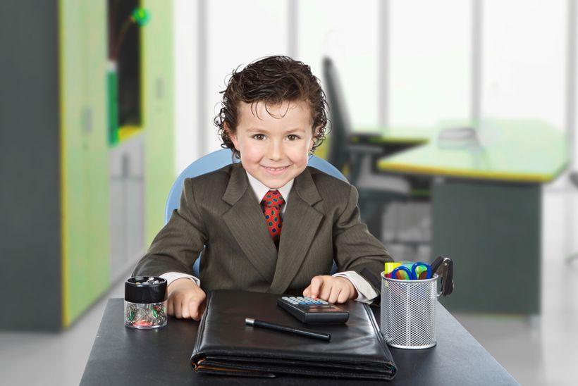 dijete u odijelu sjedi za stolom