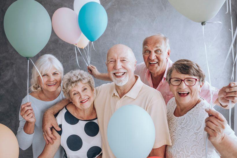 petero starijih osoba okruženih balonima