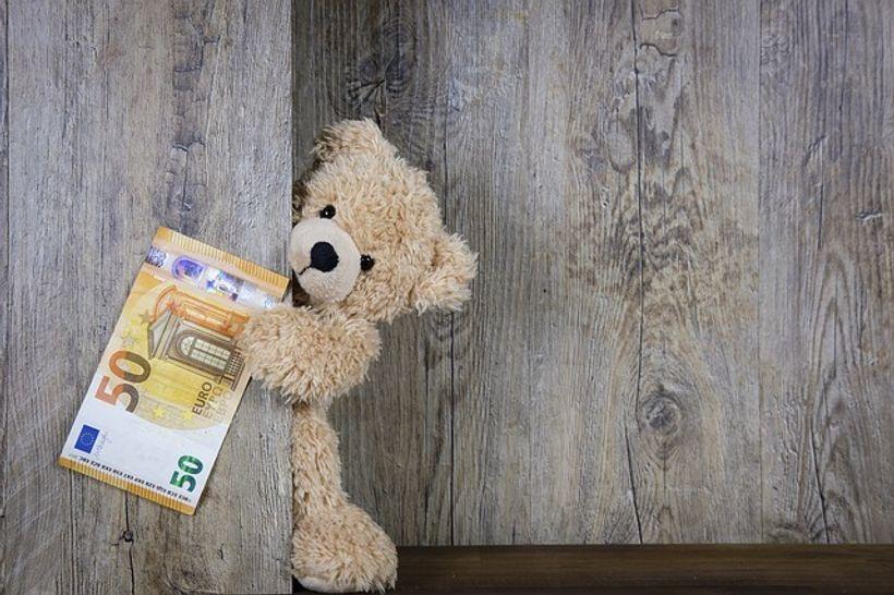 medo, mapola sakriven iza drvene pregrade, pokazuje novčanicu od 50 eura