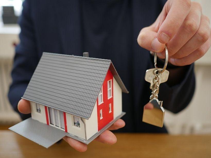 u ljudskim rukama se nalaze minijaturna kuća i ključ