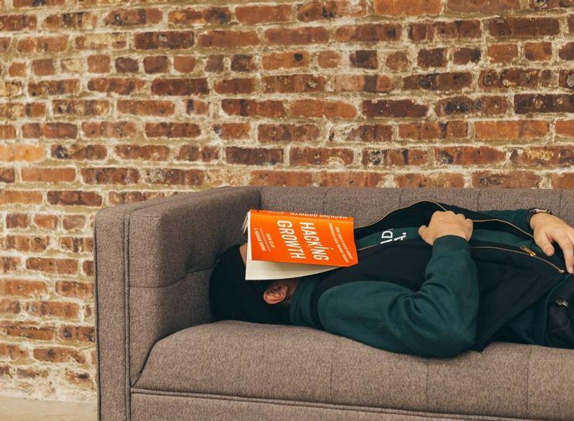 čovjek s knjigom na glavi, spava na kauču