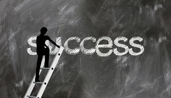 silueta se penje po stepenicama ispred ploče s natpisom ''success''