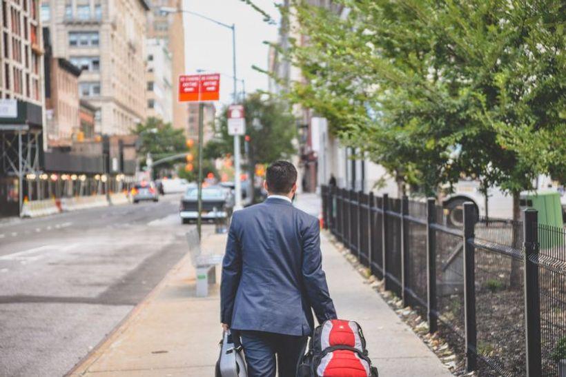 čovjek u odijelu vuče torbe i hoda ulicom