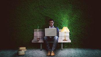 čovjek, okružen lampama, radi na laptopu