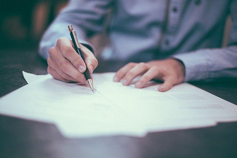 čovjek kemijskom olovkom piše po listu papira