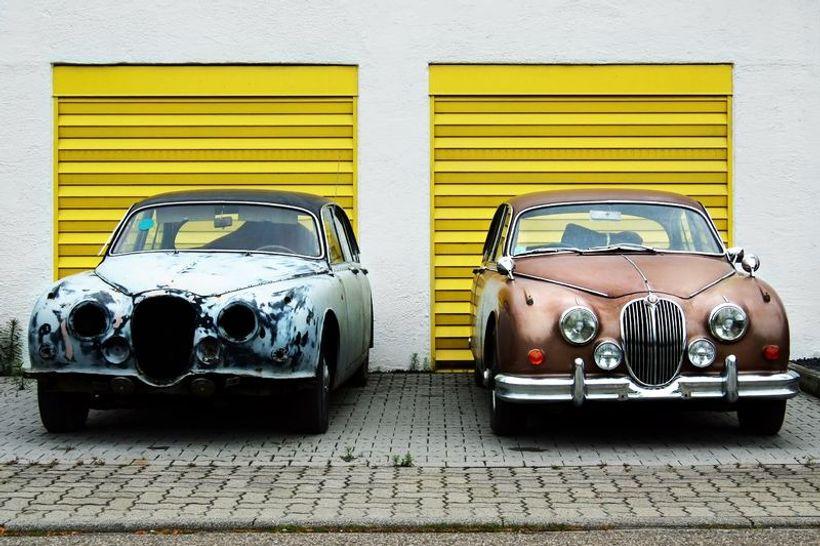 dva auta, jedan noviji, drugi stariji, parkirani ispred garaže