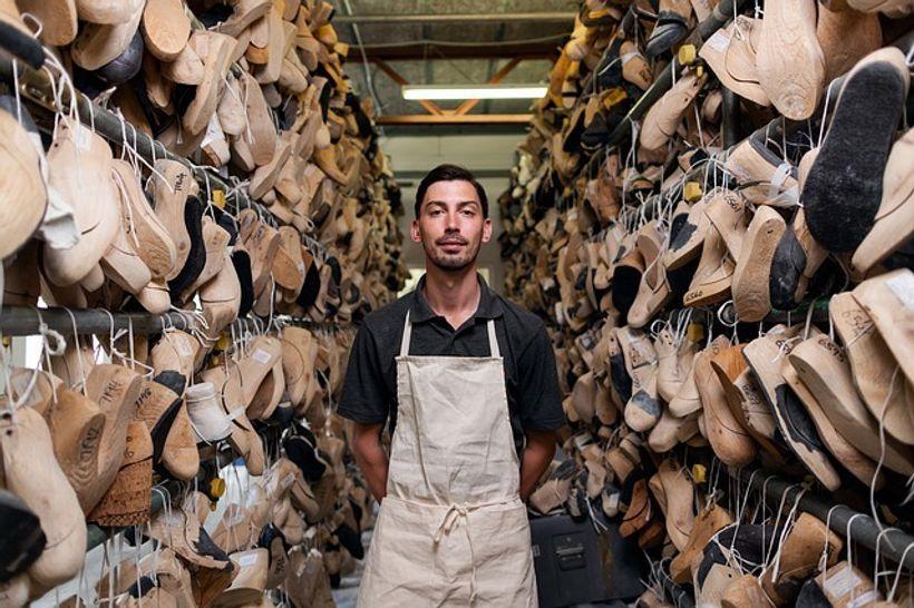 muškarac u pregači stoji u okruženju kalupa za cipele