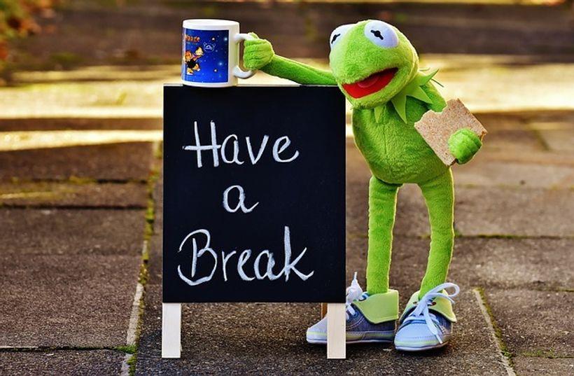 plišana žaba sa šalicom kave pored ploče s natpisom 'have a break'