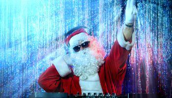 disk jockey u odijelu djeda božićnjaka za miks pultom