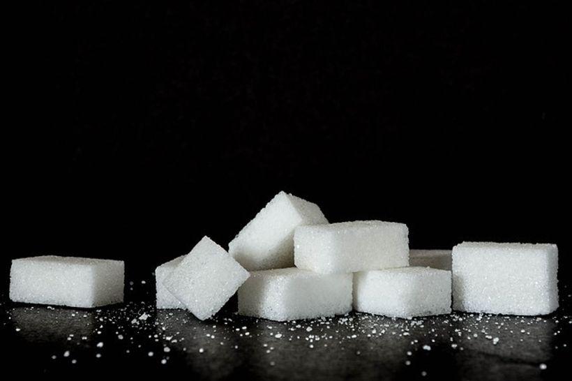 kockice šećera ispred crne pozadine