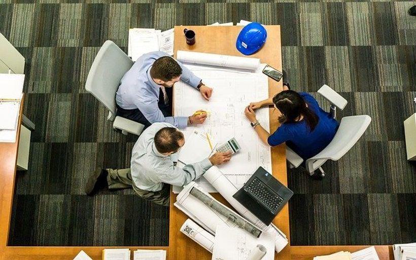 troje ljud, dvojica muškaraca u svijetloplavim košuljama i žena u plavoj bluzi, sjedi za stolomna kojem se nalaze papiri