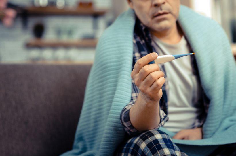 čovjek u pidžami, omotan dekom, u ruci drži toplomjer