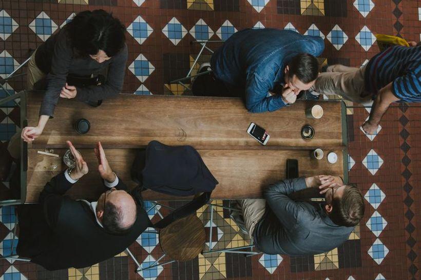 četvero ljudi sjedi za stolom