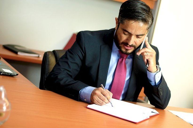 čovjek u odijelu sjedi za stolom i piše po ppiru