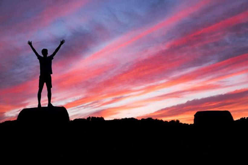 silueta muškarca stoji na stijeni a u pozadini je narančasto nebo