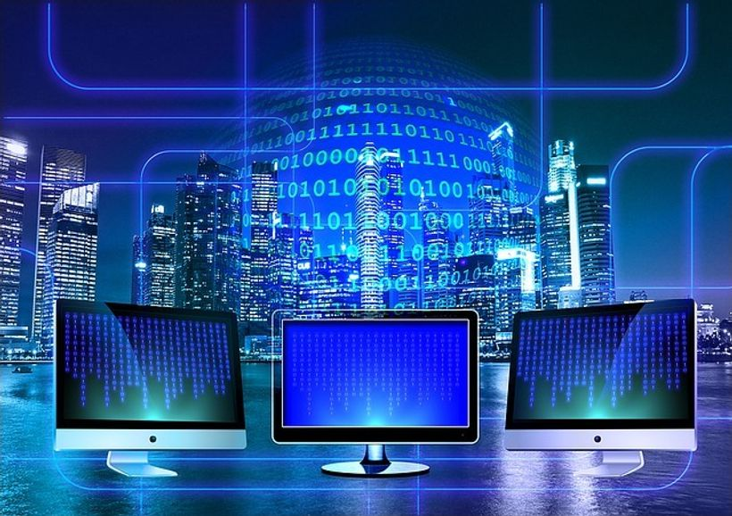 3 monitora ispred plave pozadines neboderima