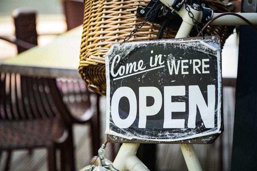 natpis 'come in we're open' obješen o košaru na biciklu