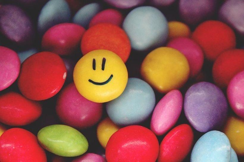 žuti , nasmiješeni bombon na hrpi šarenih bonbona