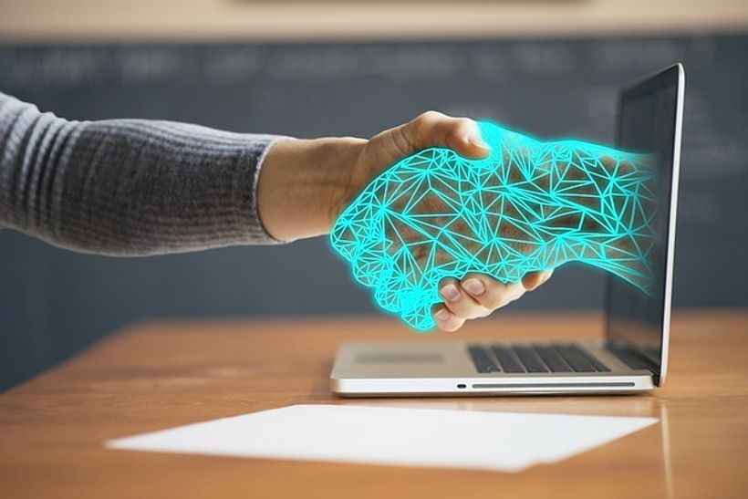 ljudska ruka se rukuje sa virtualnom rukom koja izlazi iz laptopa