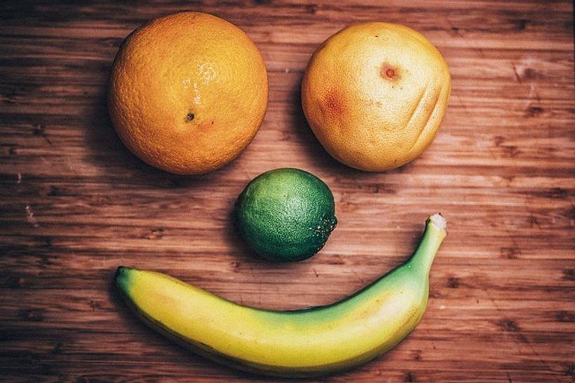 dvije naranče, limeta i banana tvore nasmiješeno lice