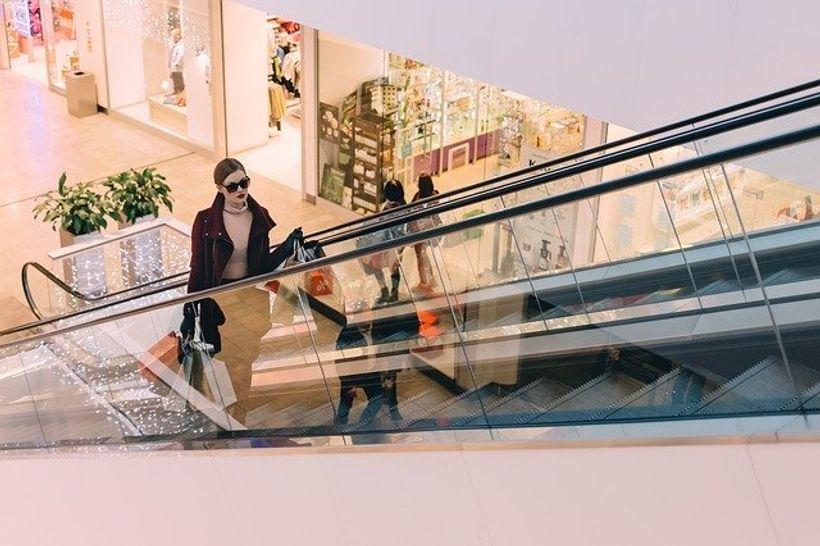 žena s vrećicama na pokretnim stepenicama