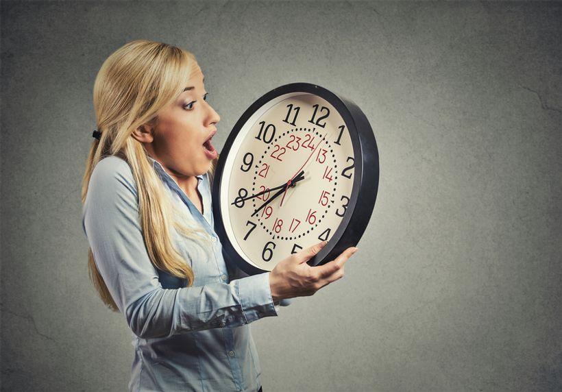 žena u rukama drži zidni sat