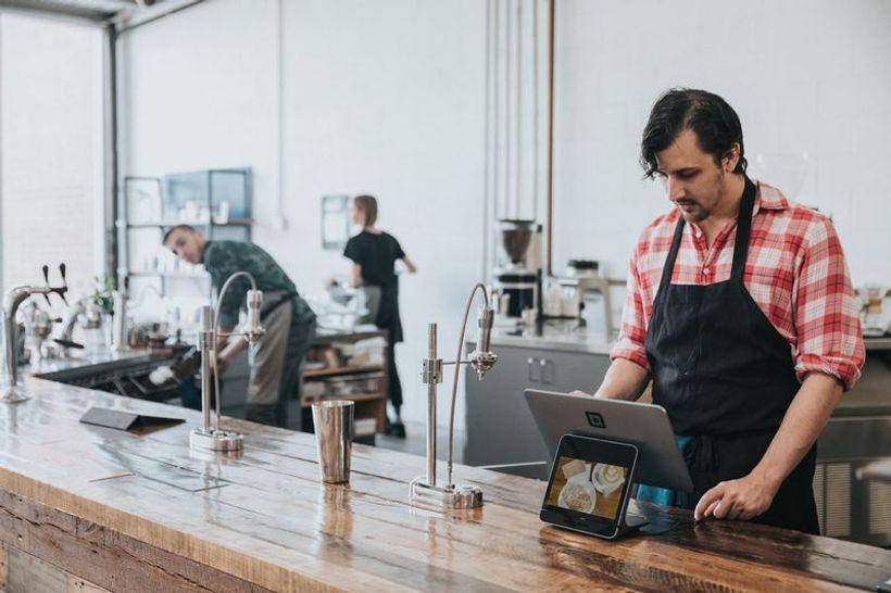 mladi muškarac u krairanoj košulji s pregačom  radi na šanku u restoranu